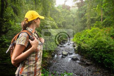 Plakat Kobieta turysta z plecakiem stałego i korzystających lesie deszczowym i widokiem na rzekę