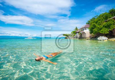 Kobieta w bikini relaksu leżąc na wodzie na tle plaży i domku.