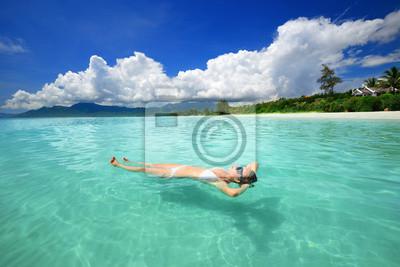 Kobieta w bikini relaksu leżąc na wodzie przed backgrou