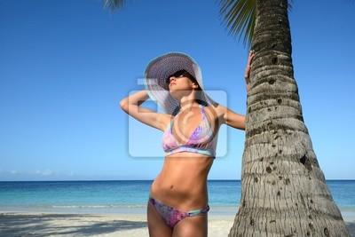 Plakat Kobieta w kapeluszu lato opalać pod palmą na tle