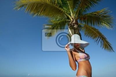 Kobieta w kapeluszu lato opalać pod palmą na tle
