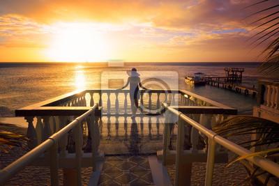 Kobieta w kapeluszu patrząc na romantyczny zachód słońca Karaibów