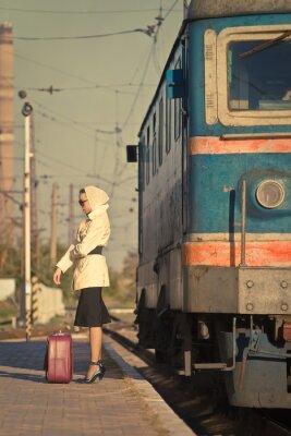 Plakat Kobieta w okularach czeka pociąg na dworzec kolejowy.
