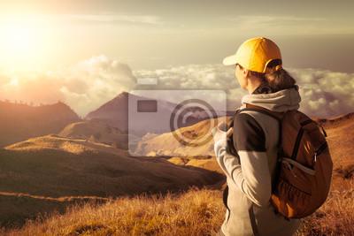Plakat Kobieta z plecakiem cieszyć widokiem na góry, w wysokich górach.