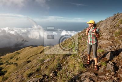 Plakat Kobieta z plecakiem cieszyć widokiem na zachód słońca w górach.
