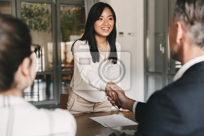 Plakat Koncepcja biznesu, kariery i umieszczenia - obraz z tyłu dwóch pracodawców siedzi w biurze i drżenie ręki młodej kobiety Azji, po udanych negocjacji lub wywiadu