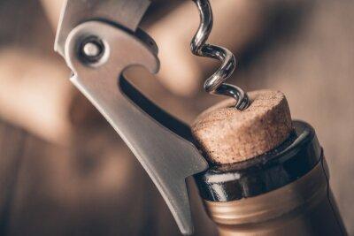 Plakat korkociągiem i wino bottleOpening butelki wina z korkociągiem w restauracji