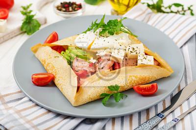Kuchnia francuska. Śniadanie, lunch, przekąski. Naleśniki z jajkiem w koszulce, serem feta, smażoną szynką, awokado i pomidorami na białym stole