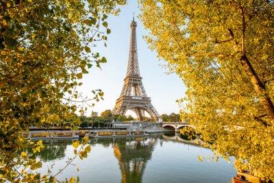 Plakat Landsacpe widok wieża eifla podczas wschodu słońca z pięknymi żółtymi drzewami w jesieni w Paryż