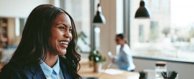 Plakat Laughing young African American businesswoman walking through an office