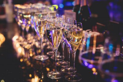 Plakat Line of alcohol setting on catering banquet table, bartender pouring beverages, row of different colored alcohol cocktails on a party, martini, vodka, and others on decorated banquet table event