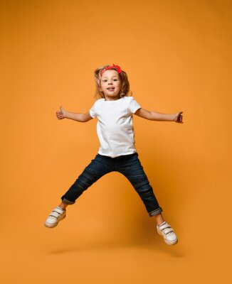 Plakat Little funny child baby girl jumping happy smiling laughing in white t-shirt with text copy space