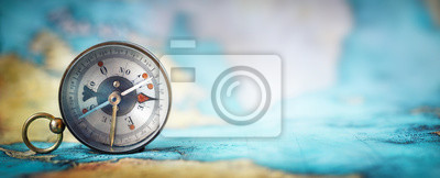 Plakat Magnetic old compass on world map.Travel, geography, navigation, tourism and exploration concept wide background. Macro photo. Very shallow focus.