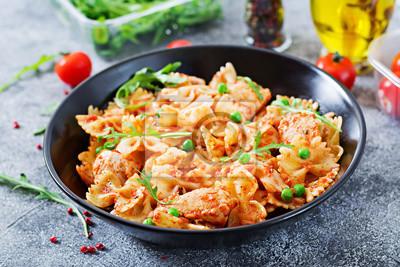Makaron farfalle z filetem z kurczaka, sosem pomidorowym i zielonym groszkiem. Domowe jedzenie. Włoski posiłek. Menu żywności