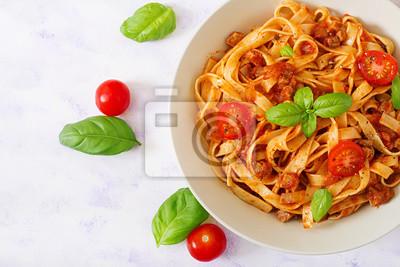 Makaron Fettuccine Bolognese z sosem pomidorowym w białej misce. Płaskie leże. Widok z góry