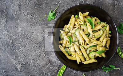 Makaron penne z sosem pesto, cukinią, zielonym groszkiem i bazylią. Włoskie jedzenie. Widok z góry. Płaskie leżało.