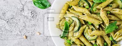 Makaron penne z sosem pesto, cukinią, zielonym groszkiem i bazylią. Włoskie jedzenie. Widok z góry. Płaskie leżało. Transparent