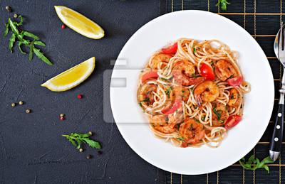 Makaron spaghetti z krewetkami, pomidorem i pietruszką. Zdrowy posiłek. Włoskie jedzenie. Widok z góry. Płaskie leżało