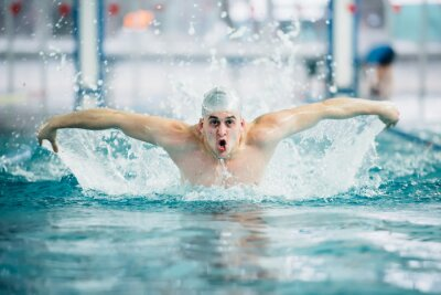 Plakat male pływakiem, wykonywania motylkowy technikę na krytym basenie. rocznika efekt
