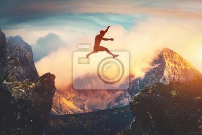 Plakat Man jumping between mountains at sunset.
