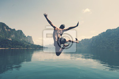 Plakat Man jumping with joy by a lake