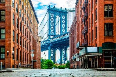 Plakat Manhattan Bridge między Manhattanem a Brooklynem nad rzeką East River widziany z wąskiej uliczki zamkniętej dwoma ceglanymi budynkami w słoneczny dzień na Washington street w Dumbo, Brooklyn, Nowy Jor