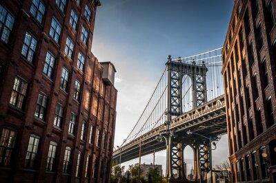 Plakat Manhattan Bridge widziany z wąskiej alejki otoczone dwóch budynków murowanych w słoneczny dzień w lecie
