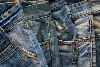 many jeans of different shades of blue lie layers nearby