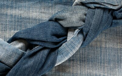 many jeans of different shades of blue lie woven oblique layers nearby