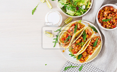 Meksykańskie tacos z kurczakiem, sosem kukurydzianym i pomidorowym. Kuchnia latynoamerykańska. Taco, tortilla, opakowanie. Widok z góry. Leżał płasko