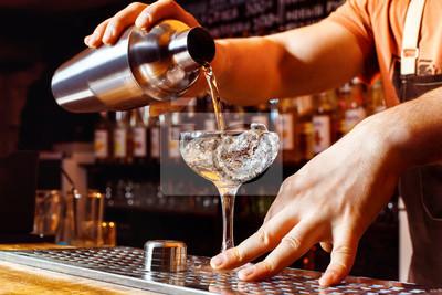 Plakat Mężczyzna Barman czyni gospodarstwa koktajl shaker z odlewania alkoholu