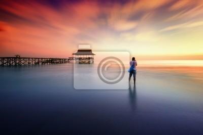 Plakat Mężczyzna sfotografował zachód słońca w pobliżu molo