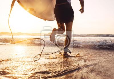 Plakat Mężczyzna surfingowiec biegający w oceanie z surfboard. Aktywne wakacje, zdrowie i wizerunek koncepcji sportu