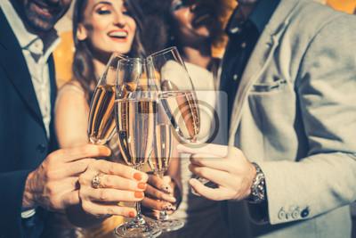 Plakat Mężczyźni i kobiety świętują urodziny lub noworoczne imprezy, podczas gdy brzęczą kieliszki z winem musującym