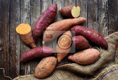 Plakat Mieszanka słodkich ziemniaków z worek na drewniane tła