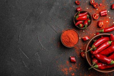 Plakat Mieszkanie leżał skład z sproszkowanych i surowych papryczek chili na ciemnym tle. Miejsce na tekst