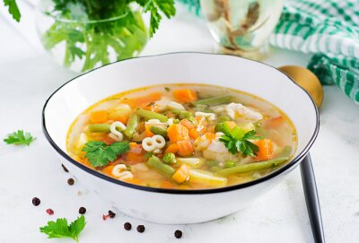 Minestrone, italian vegetable soup with pasta on light table.
