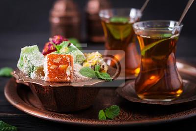 Miska z różnymi kawałkami tureckiego jedzenia lokum i czarnej herbaty z mięty na ciemnym tle
