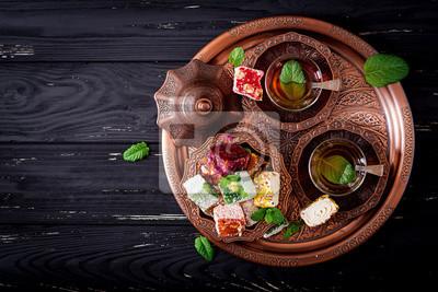 Miska z różnymi kawałkami tureckiego jedzenia lokum i czarnej herbaty z mięty na ciemnym tle drewnianym. Płaskie leże. Widok z góry
