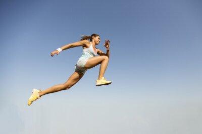 Plakat Młoda kobieta, biorąc skok w dal