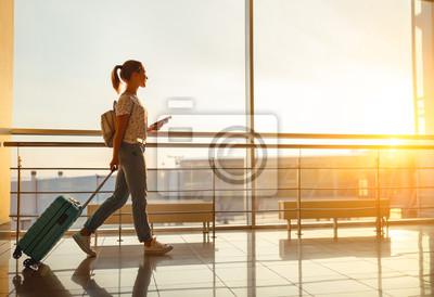 Plakat młoda kobieta idzie na lotnisko w oknie z walizką czekając na samolot