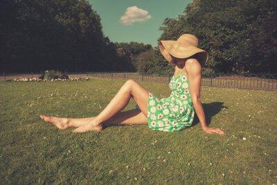 Plakat Młoda kobieta ma na sobie kapelusz i strój siedzi w parku