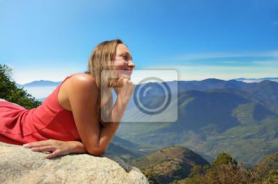 Młoda kobieta, patrząc na góry, na skraju urwiska