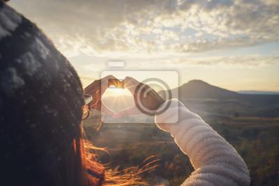 Plakat Młoda kobieta podróżnik robi kierowemu kształtowi symbolowi przy wschodem słońca