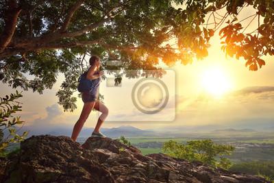 Młoda kobieta podziwia zachód słońca z plecak stojących na klifie