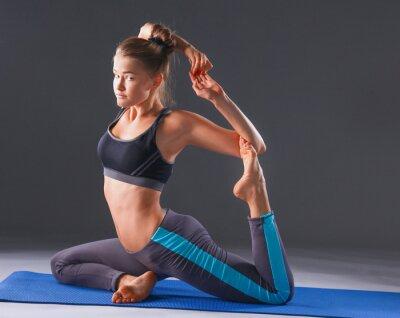 Plakat Młoda kobieta robi ćwiczenia jogi na szarym tle