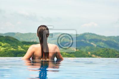 Młoda kobieta sexy korzystających spoczywającej na krawędzi swimmin zewnątrz