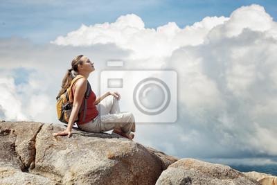 Młoda kobieta siedzi na skale z plecakiem.