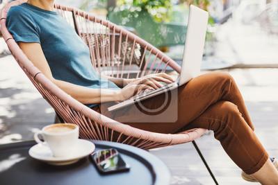 Plakat Młoda kobieta używa laptop plenerowego. Młoda piękna dziewczyna siedzi na tarasie kawiarni i pracy na komputerze