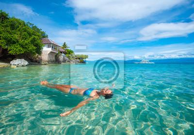 Młoda kobieta w bikini odprężającą leżącego na wodzie na tle plaży i bungalow